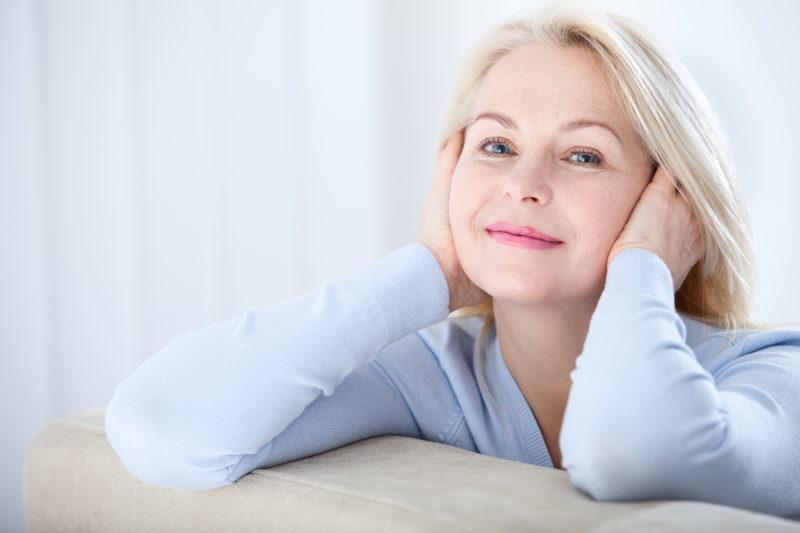 Frau mit grauen Haaren lächelt zufrieden